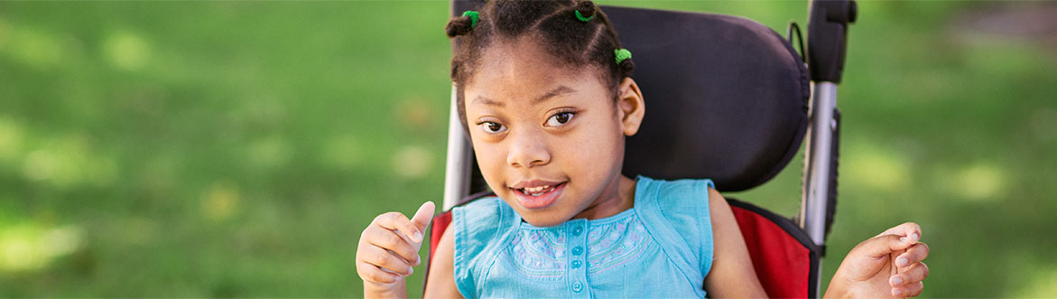 Smiling little girl sitting in a wheelchair