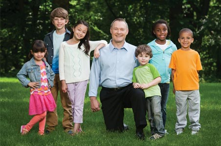 The Iowa State Treasurer poses with six diverse children