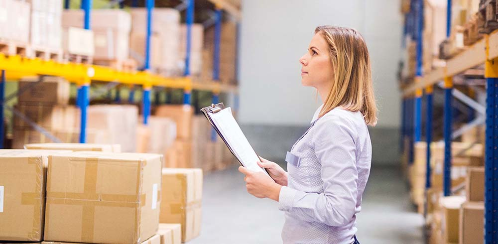 AdobeStock_190394521.jpg (Woman warehouse worker or supervisor with clipboard.)