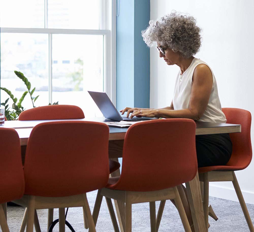 AdobeStock_186000303.jpg (Middle aged woman working alone in office boardroom)