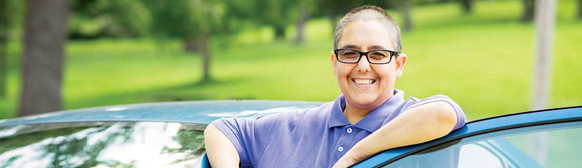 Smiling picture of woman standing by a blue car