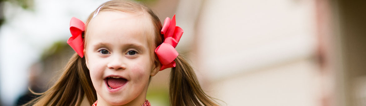 Smiling picture of girl with pink ribbons in her hair
