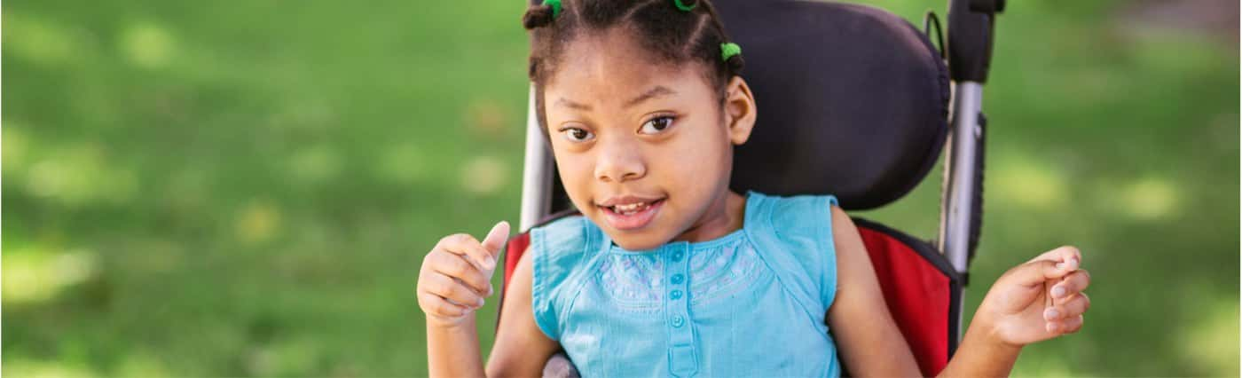 A young girl, smiling in a wheelchair in the grass.