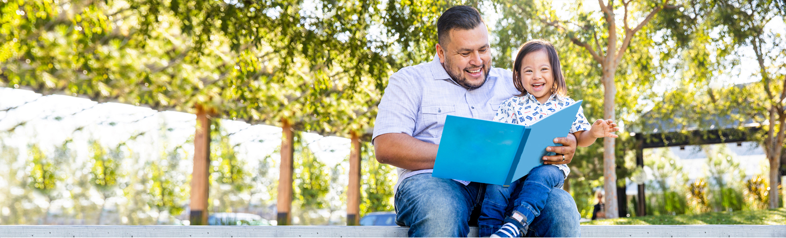 Dad sitting outside on a spring day in a park reading to his young daughter, who has Down Syndrome. Both are happy, and wearing blue jeans and short-sleeved shirts.