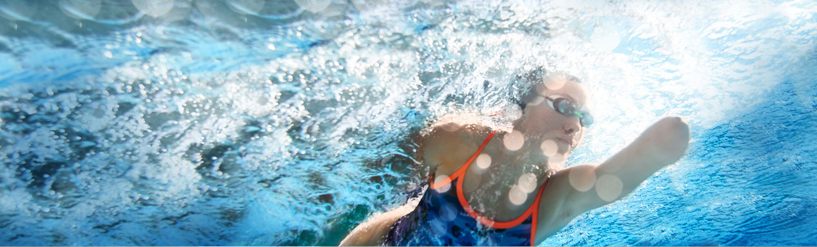 Woman with an amputated left arm below the elbow swimming laps while wearing goggles, a swim cap and a blue bathing suit with orange piping