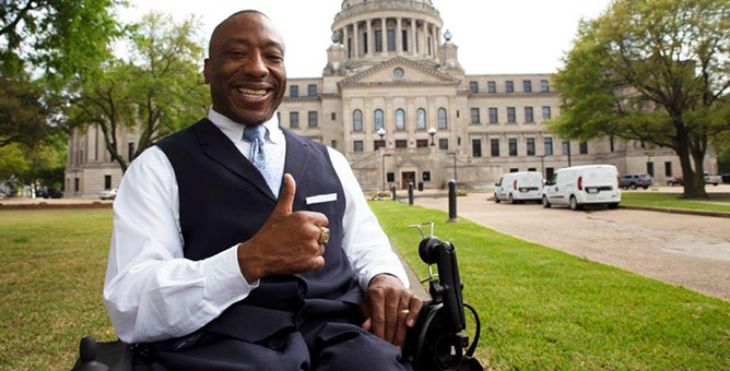 Man sitting in a wheelchair smiling