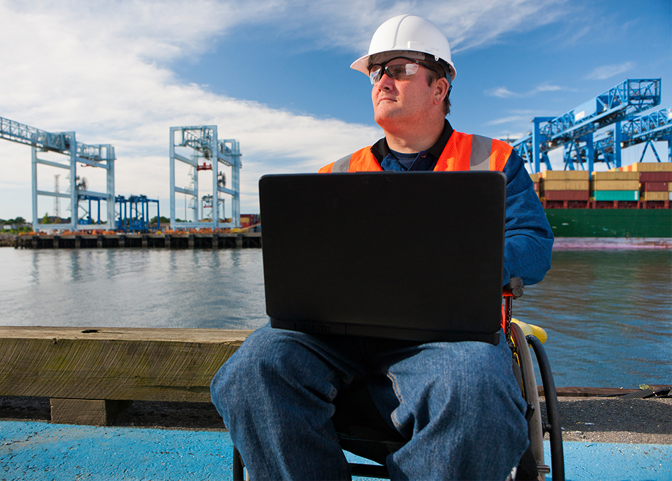 Man in wheelchair dressed with construction attire using a laptop.