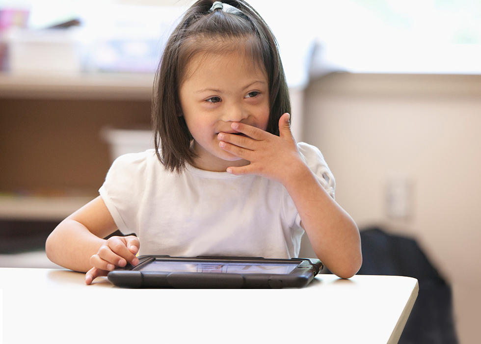 Little girl smiling while using tablet device