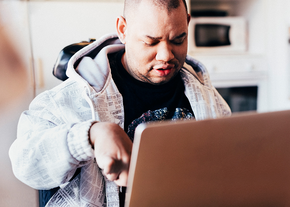 Man sitting down using a laptop