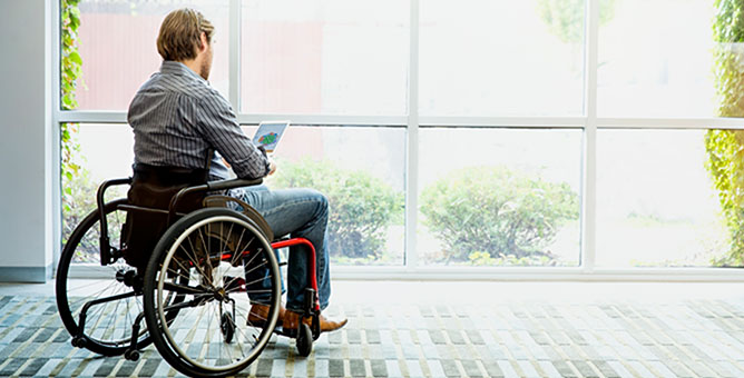 Man in wheelchair using tablet device.