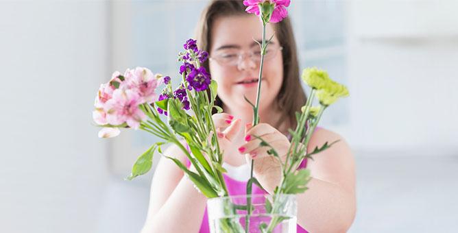 Girl placing flowers in vase.